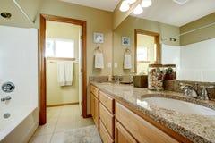 Badrumfåfängakabinett med den granitöverkanten och spegeln Arkivbilder