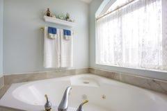 Badruminre med det agleaming badkaret bredvid ett stort välvt fönster arkivbilder