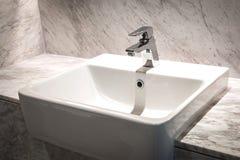 Badruminre med vasken och vattenkranen Arkivfoton