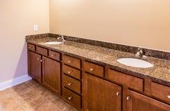 Badrumkabinetter med granitfåfänga och tegelplattagolvet Royaltyfria Foton