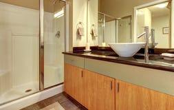 Badrummen med wood moderna skåp och vit sjunker. Arkivbilder