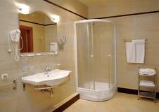 Badrummet i ljus tonar med ett duschbås Arkivfoto