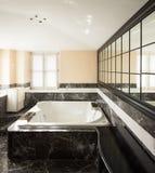 Badrummet med svarta marmortegelplattor och tömmer det stora badkaret Arkivbild