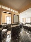 Badrummet med svarta marmortegelplattor och tömmer det stora badkaret Arkivfoto