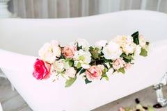 Badrummet ?r i ett ljust rum som dekoreras med blommor och kronblad av rosor royaltyfria bilder