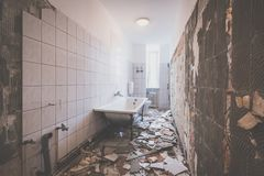Badrumrenovering - ta bort tegelplattor i gammalt lägenhetbadrum royaltyfria foton
