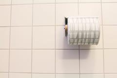 Badrumsilkespapper på den antracit belade med tegel väggen royaltyfria foton