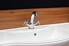 Badrumsvart och röd brun träinre med den vita vasken och den retro klassiska stilvattenkranen royaltyfria bilder
