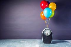 Badrumvåg med färgrika ballonger Bantningbegrepp arkivbild