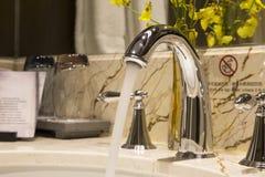 Badrumvattenkranklapp med skönhetsmedelobjekt royaltyfria bilder