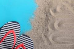 Badskor i sanden på en blå bakgrund royaltyfria bilder