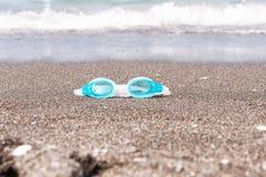 Badskyddsglasögon på sanden Arkivfoto