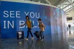 BADUNG,BALI/INDONESIA 6月25日2018年:两年轻旅行家给离开终端带来他们的手提箱在拉伊巴克罕巴厘岛 库存照片