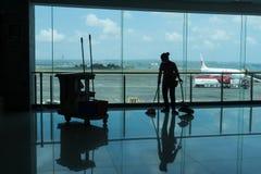 BADUNG/BALI- 28-ОЕ МАРТА 2019: силуэт привратника очищает пол отклонения терминальный с предпосылкой и airpo самолета стоковое фото rf