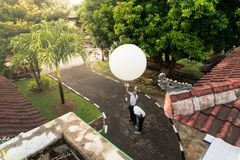 BADUNG/BALI-APRIL 10 2019: An observer at Ngurah Rai Meteorological station releasing the big white radio sonde balloon to measure stock image