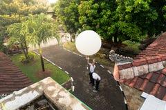 BADUNG/BALI-APRIL 10 2019: Obserwator uwalnia dużego bielu radia sonde balon mierzyć przy Ngurah Rai Meteorologiczną stacją obraz stock
