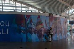 BADUNG/BALI- 28 DE MARÇO DE 2019: Um turista fêmea, levando uma mala de viagem, estava estando em uma área em um aeroporto decora fotografia de stock