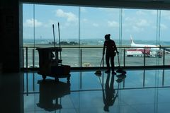 BADUNG/BALI- 28 DE MARZO DE 2019: la silueta de un portero está limpiando el piso terminal de la salida con el fondo y el airpo d foto de archivo libre de regalías