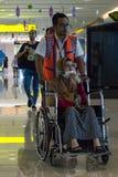 BADUNG/BALI- 25 GIUGNO 2018: La squadra di volo aiuta i passeggeri malati che per mezzo di una sedia a rotelle fotografie stock libere da diritti