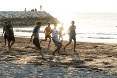 BADUNG, BALI/INDONESIA- 2-ОЕ АПРЕЛЯ 2019: Азиатские футбол или футбол игры подростка на пляже с предпосылкой захода солнца стоковые фотографии rf