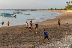 BADUNG, BALI/INDONESIA- 2. APRIL 2019: Asiatischer Jugendlichspielfußball oder -fußball am Strand mit Sonnenuntergang oder glückl lizenzfreie stockfotografie
