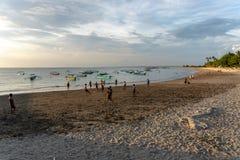 BADUNG BALI/INDONESIA-APRIL 02 2019: Asiatisk tonåringlekfotboll eller fotboll på stranden med solnedgång eller guld- timmar bakg arkivbilder