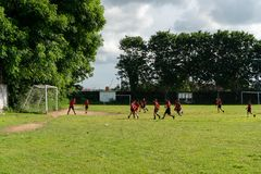 BADUNG, BALI/INDONESIA- 5. APRIL 2019: Grundlegender Studentenspielfußball oder -fußball auf dem Feld mit rotem Trikot lizenzfreie stockfotografie