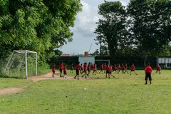 BADUNG, 05 BALI/INDONESIA-APRIL 2019: Het de elementaire voetbal of voetbal van het studentenspel op het gebied met rood Jersey royalty-vrije stock foto