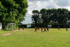 BADUNG, 05 BALI/INDONESIA-APRIL 2019: Het de elementaire voetbal of voetbal van het studentenspel op het gebied met rood Jersey royalty-vrije stock fotografie