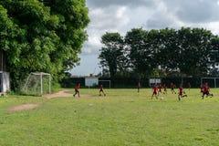 BADUNG, BALI/INDONESIA- 5 APRILE 2019: Lo studente elementare gioca a calcio o calcio sul campo con il jersey rosso fotografia stock libera da diritti