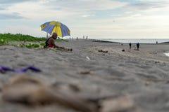 BADUNG, BALI/INDONESIA- 2 DE ABRIL DE 2019: El viejo hombre se sienta en la arena y goza el tomar el sol imágenes de archivo libres de regalías