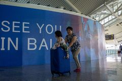 BADUNG, BALI/INDONESIA- 25 de junho de 2018: Mãe e sua filha pequena para trazer sua mala de viagem ao terminal da partida em Ngu imagens de stock royalty free