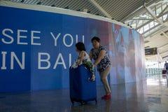 BADUNG, BALI/INDONESIA- 25 de junio de 2018: Madre y su pequeña hija traer su maleta al terminal de la salida en Ngurah Rai Bali imágenes de archivo libres de regalías