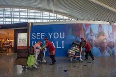 BADUNG, 25 BALI/INDONESIA-Juni 2018: De portiers brengen passagierskoffers aan vertrekterminal stock fotografie