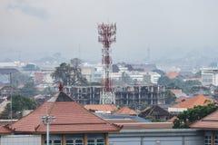 BADUNG, BALI/INDONESIA: Uma torre das telecomunicações situada em Bali, olha mais altamente do que as construções circunvizinhas foto de stock royalty free