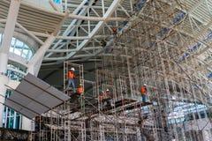 BADUNG/BALI- 28 MARS 2019 : Quelques travailleurs remontent un ?chafaudage sur le terminal international de l'arriv?e de l'a?ropo photo libre de droits