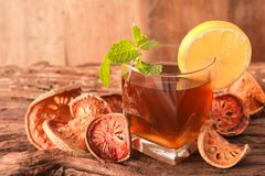 Bael fruit tea. A glass of  with lemon slices and mint leaf on a rustic wooden background. Beal beverage, Close up, Selective Focus Royalty Free Stock Image