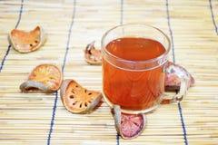 Bael fruktsaft, i klara exponeringsglasbeh?llare, med baelfruktskivor som f?rl?ggas bredvid, p? en vit bakgrund arkivfoto