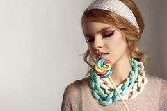 Baeutiful girl in silver dress with lolipop and necklace Stock Photos