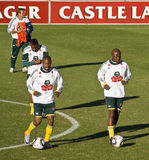 Bafana Bafana Soccer Team Practice. Bafana Bafana (South African National Soccer Team) - dribbling balls across the filed, flanked by the Castle Lager branded Stock Image