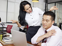 Baffled asian businesswoman. Asian businesswoman puzzled and baffled at  male colleague's behavior Royalty Free Stock Photos