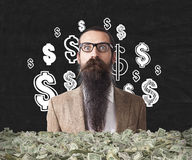 Baffled man buried in packs of dollars. Baffled man with long beard is buried in packs of dollars and standing against black wall with dollar signs. Concept of stock images