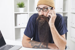 Baffled man with long beard on the phone Stock Photo