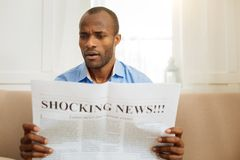 Baffled man reading shocking news. I am shocked. Concentrated astonished afro-american man holding and reading a newspaper while sitting on the sofa Stock Image