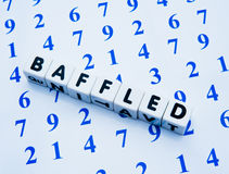 Baffled by numbers. Text ' baffled ' in black uppercase letters on small white cubes place on a surface covered by numbers in blue on white, concept of baffled Royalty Free Stock Photo