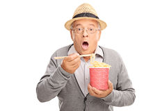 Baffled senior eating Chinese food with sticks Royalty Free Stock Images
