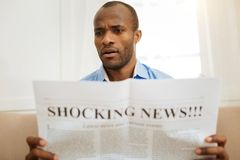Shocked man reading a newspaper. Baffled. Serious baffled afro-american man holding and reading a newspaper while sitting on the sofa Stock Photos