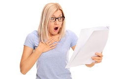 Baffled woman looking at a piece of paper in disbelief Royalty Free Stock Photography