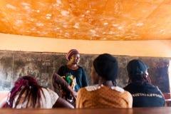 Bafoussam, Камерун - 6-ое августа 2018: усмехаться молодого африканского учителя женщины добровольный во время урока в всепокорно стоковые фотографии rf