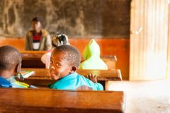 Bafoussam, Cameroon - 06 august 2018: smiling african child looking in camera during lesson in humble village school with teacher stock photography